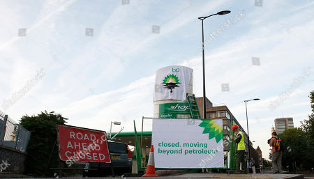 Greenpeace activists puts up a banner as they block off a British Petroleum fuel station in protest as the BP board announce their annual results, in London, . BP is jettisoning CEO Tony Hayward, whose verbal blunders made the oil giant's image even worse as it struggled to contain the Gulf oil spill, and will assign him to a key job in Russia, a person familiar with the matter said Monday