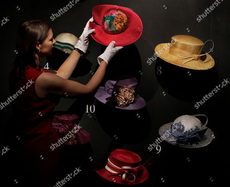 Royal Collection worker Caroline de Guitaut poses for photographs with a collection of hats Britain's Queen Elizabeth II has worn to the Royal Ascot horse race meeting over the years during a media event held to preview 'The Queen's Year' exhibition at Buckingham Palace in London, . The exhibition, which is part of the Summer Opening of the State Rooms at the palace, opens to the public on July 27 and includes displays of robes, gifts, uniforms, dresses and jewellery, giving visitors an insight into the principal national and ceremonial events in the royal year