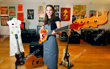Stock Photo of An employee of Christie's poses with a bass guitar owned by The Who's John Entwistle in front of other memorabilia from The Who at Christie's auction rooms, London, England, . The Who lots which are estimated to be sold at over 100,000 pounds (US$147,000, Euro 120,000 ) will be auctioned on June 24