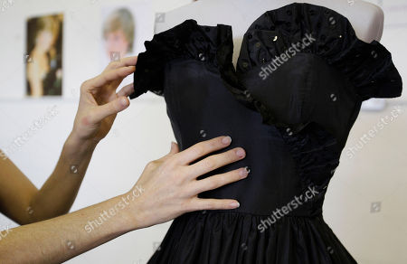 The black taffeta evening gown worn by Princess Diana on her first official appearance after her engagement to Prince Charles, designed by Elizabeth Emanuel is displayed, at an auction house in London. It was black and strapless, with a sassy sequined flounce at the bodice and a gloriously full, swishy skirt. The dress was, Lady Diana Spencer thought, so grown-up, just right for her first official engagement after the announcement she was to marry Prince Charles. The black dress is expected to fetch between 30,000 and 50,000 pounds ($44,000 to $73,000) and the prototype of the wedding dress between 8,000 and 12,000 pounds ($12,000 to $17,000) but understand that Diana's legacy means there's a strong chance a private collector may snap up the garments
