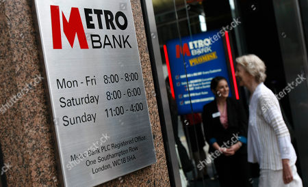 A potential customer walks into the first branch of the new British high street bank, the Metro Bank, in London, . Britain's first retail bank in more than 100 years, opened for business accompanied with an array of gimmicks to attract maximum publicity, such as the offer of biscuits for customers' dogs and free breakfasts for clients, and a business plan inspired by the model used by its co-founder, billionaire Vernon Hill, when he founded America's Commerce Bank in 1973