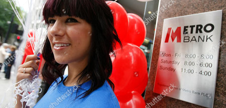 A member of the promotional team holds balloons outside the first branch of the new British high street bank, the Metro Bank, in London, . Britain's first retail bank in more than 100 years, opened for business accompanied with an array of gimmicks to attract maximum publicity, such as the offer of biscuits for customers' dogs and free breakfasts for clients, and a business plan inspired by the model used by its co-founder, billionaire Vernon Hill, when he founded America's Commerce Bank in 1973