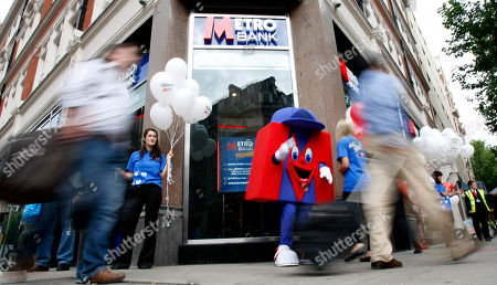 Pedestrians walk past the first branch of the new British high street bank, the Metro Bank, in London, . Britain's first retail bank in more than 100 years, opened for business accompanied with an array of gimmicks to attract maximum publicity, such as the offer of biscuits for customers' dogs and free breakfasts for clients, and a business plan inspired by the model used by its co-founder, billionaire Vernon Hill, when he founded America's Commerce Bank in 1973