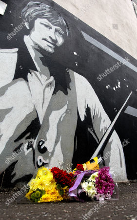 Flowers lie on the ground beside a mural depiction of snooker legend Alex Higgins in the Donegal Road area of South Belfast, Northern Ireland, . A book of condolence has been opened Monday for their hometown Belfast boy snooker star known as 'Hurricane', at Belfast City Hall. Higgins, who won the world snooker championships in 1972 and 1982, was found dead in his flat in the Sandy Row area of Belfast on Saturday, where he had suffered from throat cancer for about ten years