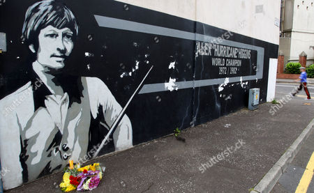 Flowers lie on the ground beside a mural depiction of snooker legend Alex Higgins in the Donegal Road area of South Belfast, Northern Ireland, . A book of condolence has been opened Monday for their hometown Belfast boy snooker star known as 'Hurricane', at Belfast City Hall. Higgins, who won the world snooker championships in 1972 and 1982, was found dead Saturday in his flat in the Sandy Row area of Belfast on Saturday, where he had suffered from throat cancer for about ten years
