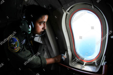 Coast Guard petty officer 3rd class Bobby Lopez views the looks out the window of a Coast Guard plane at th Deepwater Horizon oil spill in the Gulf of Mexico off the coast of Louisiana