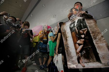 Fans of Hong Kong model and actress Chrissie Chau queue up for her autograph outside Hong Kong's exhibition and convention center on . Chau and other models were promoting their new photo books on the first day of Hong Kong's annual book fair