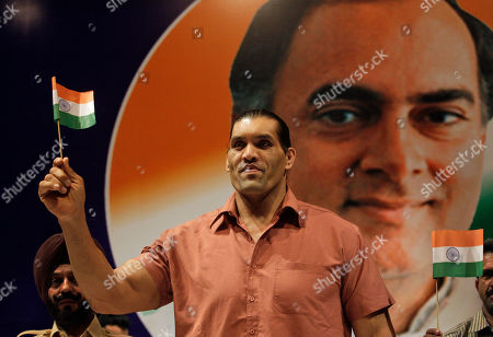 Stock Picture of The Great Khali World Wrestling Entertainment wrestler The Great Khali waves an Indian flag in the backdrop of a portrait of former Indian Prime Minister Rajiv Gandhi as he arrives for an event to honor families of soldiers killed in a recent attack by Maoist in central India's Dantewada area, in New Delhi, India, . The rebels, who have tapped into the rural poor's growing anger at being left out of the country's economic gains, are now present in 20 of the country's 28 states. About 2,000 people, including police, militants and civilians, have been killed over the past few years