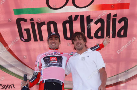 David Duran Arroyo, Fernando Alonso Spain's David Duran Arroyo, left, wearing the pink jersey of overall leader of the race, is congratulated by his fellow-countryman Fernando Alonso, on the podium after the 16th stage of the Giro d'Italia, tour of Italy cycling race, an individual time trial from San Vigilio Marebbe to Plan de Corones