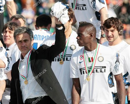 Inter Milan coach Jose Mourinho, left, celebrates his Serie A title flanked by forward Mario Balotelli, at the end of the soccer match between Siena and Inter Milan in Siena, Italy, . Inter Milan beat Siena 1-0 Sunday to seal its fifth consecutive Serie A title and move two-thirds of the way to a possible treble. Inter finished with 82 points, two more than AS Roma, which won 2-0 at Chievo Verona