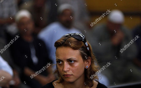 Stock Photo of Zahra, the sister of slain man Khaled Said, foreground, looks on while in the background relatives of two Egyptian policemen Mahmoud Salah and Awad Ismail, unseen attend their trial session at the court house in Alexandria, Egypt . Two Egyptian policemen charged with brutality in the death of a young Alexandria man have gone on trial in a case that sparked calls to end what activists describe as rampant police abuses in the country