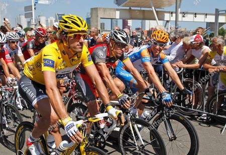 Fabian Cancellara, Lance Armstrong, Christian Vandevelde Fabian Cancellara of Switzerland, wearing the overall leader's yellow jersey, Lance Armstrong of the US, and Christian Vandevelde of the US, left to right, ride during the parade of the first stage of the Tour de France cycling race over 223,5 kilometers (139 miles) with start in Rotterdam, Netherlands and finish in Brussels, Belgium