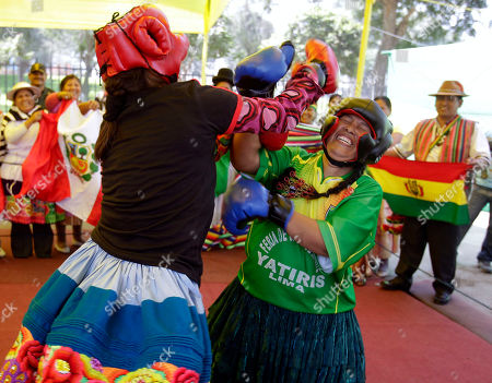 Peru's Lucy Simon, left, aka 'kickboxing', fights against Bolivia's Janette Aymituma, aka 'Iron hand', during an Andean Women Boxing exhibition in Lima