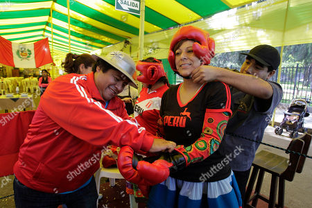Peru's Lucy Simon, center, aka 'kickboxing', prepares to fight Bolivia's Janette Aymituma, aka 'Iron hand', during an Andean Women Boxing exhibition in Lima