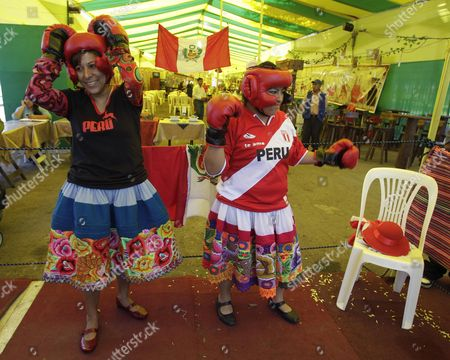 Peru's Lucy Simon, left, aka 'kickboxing' and Lidia Chavez, aka 'Kina', warm up before fighting Bolivian boxers during an Andean Women Boxing exhibition in Lima