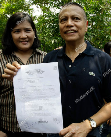 Former Philippine Marine Col. Ariel Querubin shows the document for his provisional liberty as his wife Maria Flor stands beside him at the headquarters of the Armed Forces of the Philippines in suburban Quezon City, north of Manila, Philippines. Querubin was detained for four years after figuring in a failed attempt to overthrow the administration of former President Gloria Macapagal Arroyo