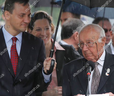"""Radek Sikorski,Simcha Rotem-Ratayzer Polish Foreign Minister Radek Sikorski, left, holds an umbrella to shelter Simcha Rotem-Ratayzer,right, a former insurgent in the Warsaw Ghetto Uprising from the rain, in Warsaw, Poland, on . Rotem-Ratayzer, whose nom-de-guerre was Kazik, was a 19-year-old in 1943 when he led the last group of fighters out of the ghetto through sewage canals to the """"Aryan"""" side of the city. Polish officials honored Rotem-Ratayzer as they unveiled a new monument in the Polish capital, once home to Europe's largest Jewish community, honoring the Jewish insurgents"""