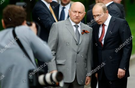 """FILE PICTURE Russian Prime Minister Vladimir Putin, right, and Moscow Mayor Yuri Luzhkov, center, attend a ceremony to lay a corner stone for a war memorial, a replica of a destroyed memorial in Kutaisi, in Victory Park on Poklonnaya Hill on the eve of Victory Day in Moscow. Russia's president fired Moscow mayor Yury Luzhkov on Tuesday, Sept. 28, 2010 ending the 18-year reign of a man who gave the crumbling capital a glamorous facelift but was maligned for his bellicose posturing and staying on vacation while forest fires choked his city. President Dmitry Medvedev signed a decree relieving the 74-year-old mayor of his duties due to a """"loss of confidence"""" in him, according to the Kremlin. With the long-awaited move, Prime Minister Vladimir Putin and Medvedev sent a powerful signal that no regional leader is indispensable"""