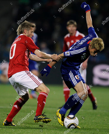 Japan's Keisuke Honda, right, competes for the ball with Denmark's Martin Jorgensen, left, during the World Cup group E soccer match between Denmark and Japan at Royal Bafokeng Stadium in Rustenburg, South Africa