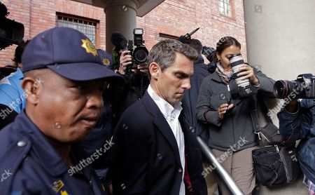 Surrounded by photographers and reporters, British journalist Simon Wright walk's out of court in the city of Cape Town, South Africa, . The British journalist accused of conspiring in the trespassing act on an England fan who entered the team's dressing room after its draw against Algeria, was ordered to reappear in court next month after being released on 3,000-rand ($390) bail
