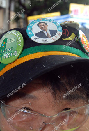 A supporter of former Taiwan President Chen Shui-bian bears Chen's portrait on her hat as he arrives at the Taiwan High Court in Taipei, Taiwan, . TV stations in Taiwan said the court has rejected Chen's appeal of his conviction on graft charges, but cut his life sentence to 20 years on Friday