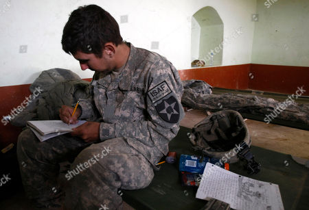 """On, U.S. Army Pvt. Mark Goodwin, 21, from Mt. Holly, North Carolina, of the 1st Battalion, 17th Infantry Regiment, 5th Stryker Brigade, 2nd Infantry Division, writes to his fiancee Jillian De Voe as he sits on his stretcher inside a U.S. Army compound in the Badula Qulp area, West of Lashkar Gah in Helmand province, southern Afghanistan. He proposed to her on Oct. 6, and she made him say """"Will you marry me?"""" over and over because she liked the sound of it. He proposed again on her birthday four days later, and this time he got down on one knee with a diamond ring. His mother was on the phone, listening in as a witness"""