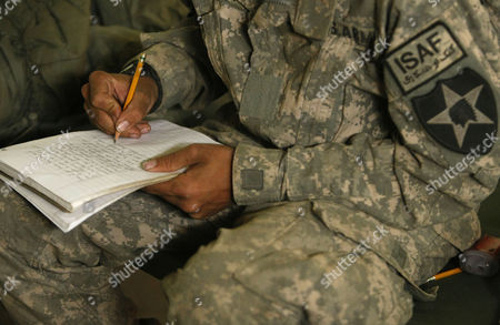 U.S. Army Pvt. Mark Goodwin, 21, from Mt. Holly, N.C., of the 1st Battalion, 17th Infantry Regiment, 5th Brigade, 2nd Infantry Division, writes to his fiancee Jillian De Voe as he sits on his cot inside a U.S. Army compound in the Badula Qulp area, West of Lashkar Gah in Helmand province, southern Afghanistan. Goodwin proposed to De Voe on Oct. 6, 2009, several days before his deployment to Afghanistan