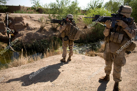 Stock Picture of Lance Cpl. Ard Bizahaloni of Pinon, Ariz., front, and Lance Cpl. Jeremy Ford with the First Battalion, Sixth Marine Regiment, Alpha company, scan the area with their M-16 rifles in Marjah, Afghanistan. The U.S. military's workhorse rifle, used in battle for the last 40 years, is proving less effective in Afghanistan, where the Taliban's more primitive but longer range weapons can threaten NATO forces at distances too great for American soldiers to return fire effectively