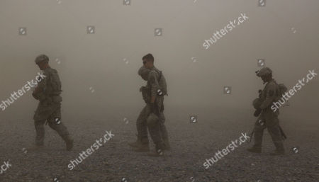 U.S. Army soldiers from Charlie Company, 2nd Battalion, 1st Infantry Regiment, head for their tents after a patrol as a sandstorm begins to blow over their forward base, in Afghanistan's Kandahar province