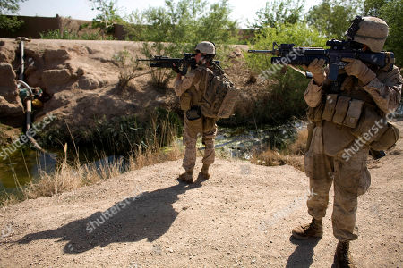 Stock Photo of Lance Cpl. Ard Bizahaloni of Pinon, Ariz., front, and Lance Cpl. Jeremy Ford with the First Battalion, Sixth Marine Regiment, Alpha company, scan the area with their M-16 rifles in Marjah, Afghanistan. The U.S. military's workhorse rifle, used in battle for the last 40 years, is proving less effective in Afghanistan, where the Taliban's more primitive but longer range weapons can threaten NATO forces at distances too great for American soldiers to return fire effectively