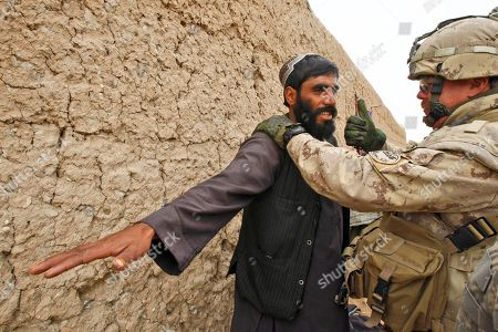 Stock Picture of Canadian Warrant Officer Peter Coyle, a medic from Toronto who is advising the Afghan National Army, treats a villager in the Badula Qulp area, West of Lashkar Gah in Helmand province, southern Afghanistan