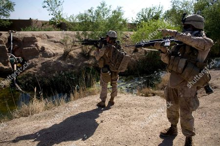 Stock Image of U.S. Marines, Lance Cpl. Ard Bizahaloni of Pinon, Arizona, front, and Lance Cpl. Jeremy Ford with the First Battalion, Sixth Marine Regiment, Alpha company, check out a suspicious movement as they are involved in a gunbattle during a patrol in Marjah, Afghanistan