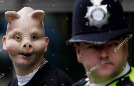 A British police officer, right, guards a protester, left, wearing a pig mask demonstrating against the parliamentarians' expenses scandal outside the Westminster Magistrates Court in central London, . Britain's Conservatives party Lord Hanningfield and Labour party's Jim Devine, Elliot Morley and David Chaytor were in the court facing charges of false accounting in relations to their expenses claims. Police began investigating after details of all MPs' expenses claims were leaked to a national newspaper. The three MPs are currently suspended by Labour and Lord Hanningield suspended by the Conservatives
