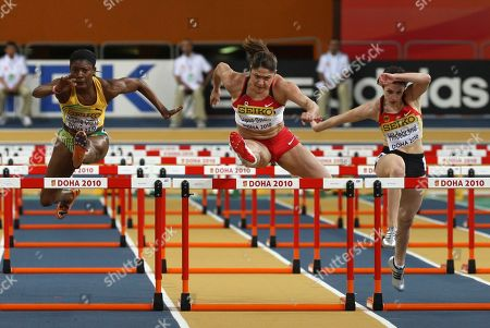 Germany's Nadine Hildebrand, Canada's Priscilla Lopes-Schliep and Jamaica's Lacena Golding-Clarke, from right, clear a hurdle during a Women's 60m hurdles heat at the 13th IAAF World Indoor Championships in in Doha, Qatar