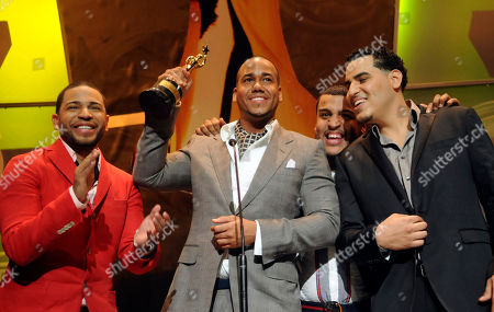 "Anthony Romeo Santos, Henry Santos, Mikey Santos, Lenny Santos Anthony ""Romeo"" Santos, second left, raises the statuette as Henry, left, Mikey, right, and Lenny of the bachata group Aventura, look, after receiving the main Casandra award, El Soberano or The Sovereign, during a ceremony at the National Theater in Santo Domingo"