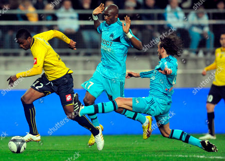 Marseille's Stephane Mbia Etoundi and Gabriel Heinze, right, challenges for the ball with Sochaux's Aide brown Ideye during their French League One soccer match at the Bonal Stadium in Sochaux, eastern France