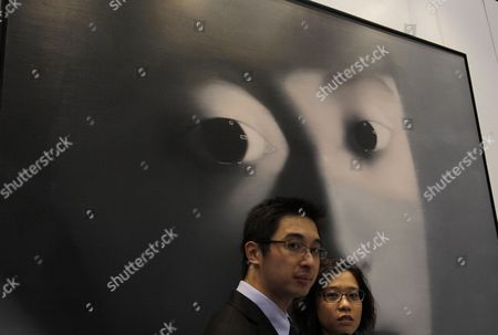 "Staffs stand in front of the painting ""Untitled"" created by Chinese artist Zhang Xiaogang during a preview of the Sotheby's Contemporary Asian Art in Hong Kong . The painting is expected to fetch US$555,000-645,000"