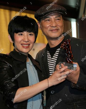 """Simon Yam, Sandra Ng Hong Kong actor Simon Yam, right, and actress Sandra Ng pose with the Berlin International Film Festival Crystal Bear prize for their movie """"Echoes of a Rainbow"""" during a press conference in Hong Kong . Hong Kong on Monday celebrated a rare foreign film prize for a low-budget family drama set in the 1960s a triumph viewed as a huge moral boost for a struggling industry overshadowed by the booming Chinese market"""