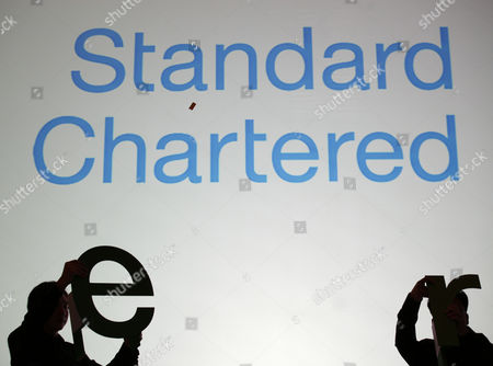 Workers prepare decorations during a news conference as Group Chief Executive of Standard Chartered PLC Peter Sands unveils the bank's new worldwide brand promise during a news conference in Hong Kong