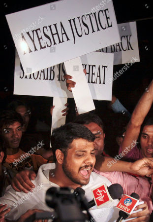 Supporters of Ayesha Siddiqui, the woman claiming to be Pakistani cricketer Shoaib Malik's wife, shout slogans against Malik outside Siddiqui's residence in Hyderabad, India, . Hyderabad police have questioned Malik about Siddiqui and have asked him not to leave India during investigation ahead of his planned marriage to Indian tennis star Sania Mirza