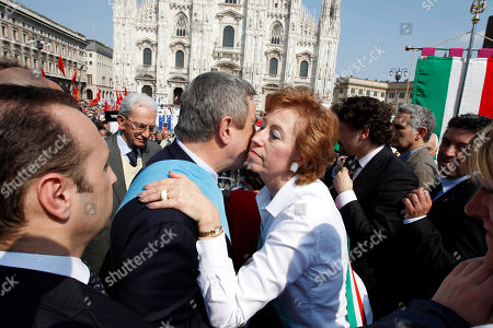 """Stock Picture of Milan's mayor Letizia Moratti, right, kisses president of the """"Provincia"""" Guido Podesta' on the occasion of the Liberation Day, in front of Milan's gothic cathedral, Italy, . The day commemorates the liberation of Italy from Nazi occupation during WWII"""
