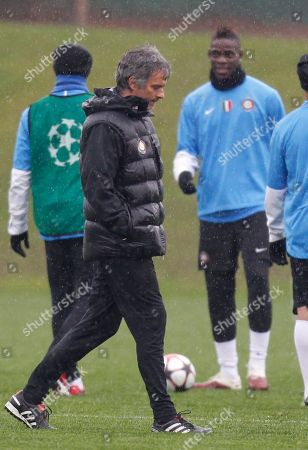 Inter Milan coach Jose' Mourinho of Portugal walks as Inter Milan forward Mario Balotelli looks on during a training in view of the Champions League quarterfinal match against CSKA of Moscow, at the team's facility in Appiano Gentile, Italy