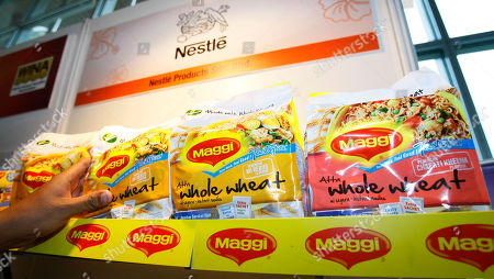 """On, a man picks up a package of Maggi instant noodle made of whole wheat manufactured by Nestle Malaysia at the 7th World Instant Noodle Summit in Kuala Lumpur, Malaysia. More than a half-century after his father invented instant noodles to feed Japan's war-ravaged masses, Koki Ando says it is time to change the high-calorie, salt-laden fast food into healthier fare for the fastidious. In Malaysia, leading manufacturer Maggi is promoting """"Tastylite"""" soup noodles made of whole wheat, with every packet providing the same amount of fiber as nearly one-and-a-half slices of whole wheat bread"""
