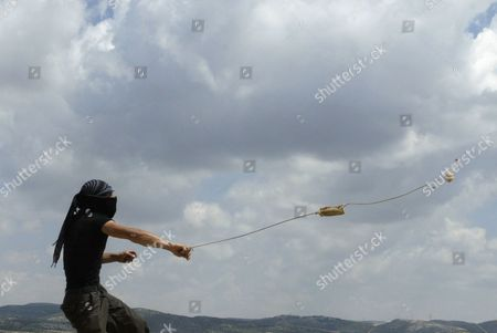 A Palestinian protester uses a sling-shot to hurl a stone at Israeli troops, not seen, during a demonstration against Israel's separation barrier, in the West Bank village of Bilin near Ramallah, . U.S. Mideast envoy George Mitchell tried Friday to get Israelis and Palestinians talking again after more than a year of deadlock, while confronting a second challenge navigating the rocky relations between Israel and the U.S