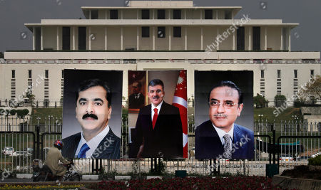 A motorcyclist drives past huge portraits of Turkish President Abdullah Gul, center, Pakistani President Asif Ali Zardar, right, and Yousuf Raza Gillani on display in front of presidency in Islamabad, Pakistan on . Gul will arrive on Tuesday evening on a four-day official visit to Pakistan to hold talks with Pakistani leadership discuss a range of issues, including security and counter-terrorism and development