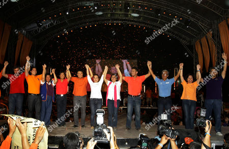 Presidential candidate Senator Manny Villar fifth from left and his vice presidential candidate Senator Loren Legarda center, raise their hands together with their senatorial candidates during their major campaign sortie in Manila's urban poor area of Tondo, Philippines. Villar, considered to be the richest among the candidates have showed a poor ratings during the last survey where he slids down a few days before the May 10 elections