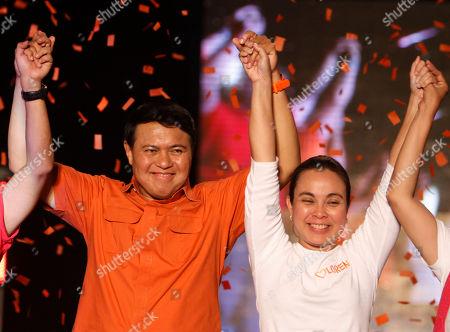 Presidential candidate Senator Manny Villar left, raises the hand of his running mate vice presidential candidate Senator Loren Legarda during their major campaign sortie in Manila's urban poor area of Tondo, Philippines