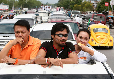 Manny Pacquiao, Manny Villar, Loren Legarda Nationalista Party Vice-Presidential candidate Loren Legarda bites her sandwich as Filipino boxing great Manny Pacquiao, center, and Presidential candidate Manny Villar, left, prepare to greet supporters along the way of their motorcade from General Santos to Sarangani province in southern Philippines. Pacquiao, who recently won a unanimous WBO Welterweight crown versus Joshua Clottey of Ghana, is now concentrating on another fight in the political arena as a candidate for congressman in nearby Sarangani province also in southern Philippines