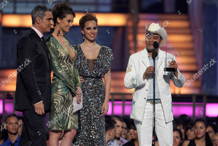 El Trono de Mexico, Stefania Fernandez, Miguel Varoni A member of the band El Trono de Mexico accepts one of two awards on behalf of the band at the 2010 Billboard Latin Music Awards in San Juan, Puerto Rico, . El Trono de Mexico won the Regional Mexican Album of the Year award and the Regional Mexican Albums Artist of the Year, Duo or Group award. At left is Colombia's Argentine born actor Miguel Varoni and Miss Universe 2009 Stefania Fernandez, of Venezuela. The woman third from left is unidentified