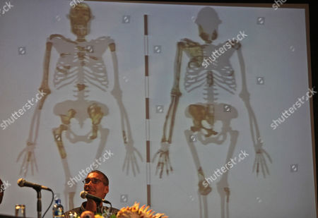 Lee Berger Professor Paul Dirksr, of the University of the Witwatersrand, in front of projected images, at the reveal of nearly 2 million-year-old skeletons unearthed in South Africa, at Maropeng, near Johannesburg, . The fossils are part of a previously unknown species that scientists say fits the transition from ancient apes to modern humans